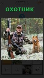 на снегу на одном колене сидит охотник с ружьем и с собакой рядом