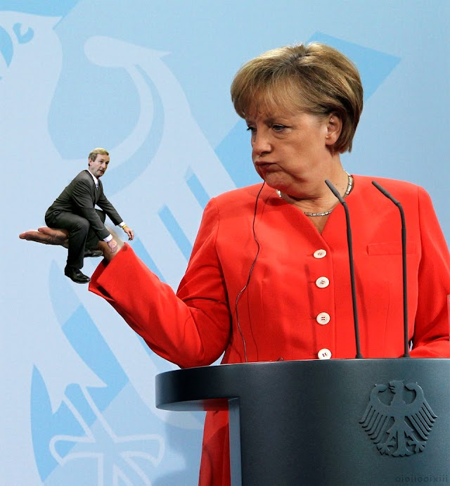 A miniature Enda Kenny sits in the palm of Angela Merkel