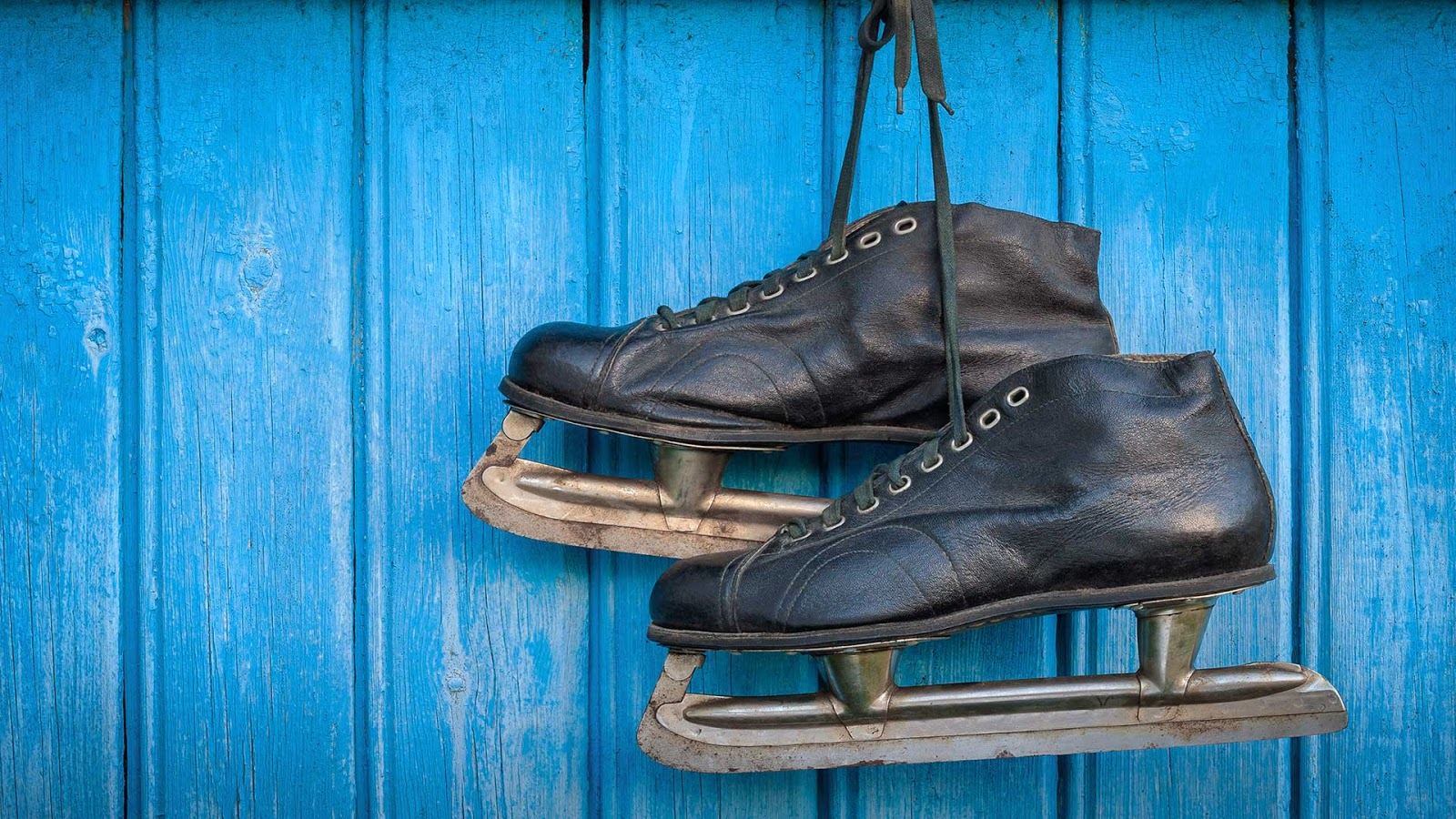 Old hockey skates hanging on a wall