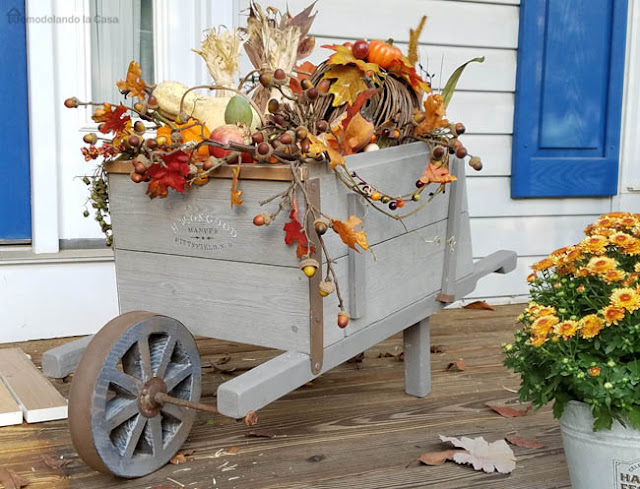 front porch decorated with rustic wheelbarrow