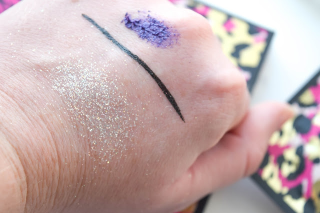 a picture of  Better Than Sex Mascara in Purple, Sketch Marker Liquid Art Eyeliner in Deep Black, Glamour Dust Glitter Pigment in Glitterally (swatch)