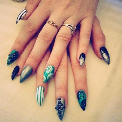 Diseño de uñas Stiletto verde, negro y rayas.