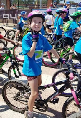 Girl with bicycle and attire for Telkom 947 Kiddies Ride