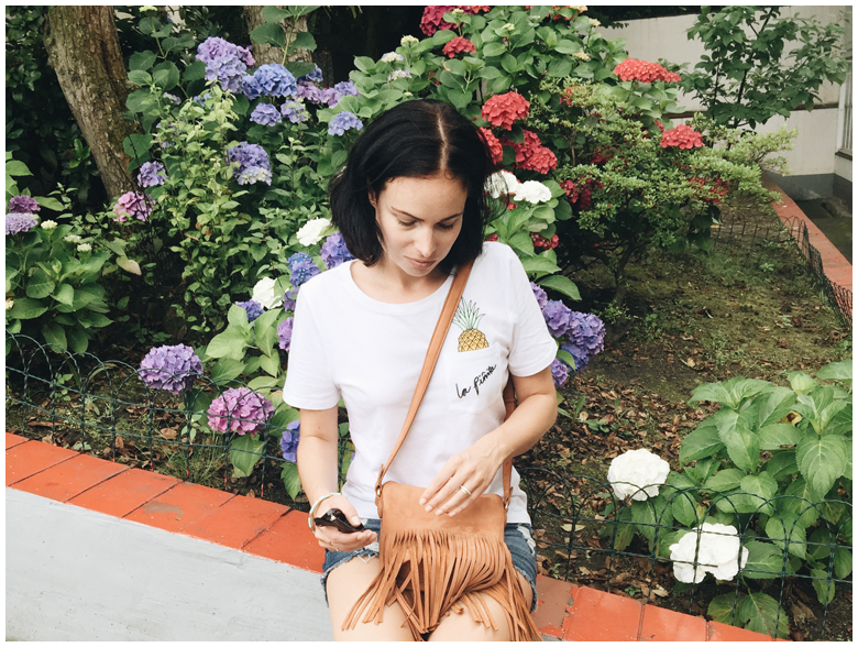 LA PINITA | June Gold wearing white pineapple printed H&M shirt and brown & Other Stories fringed bag