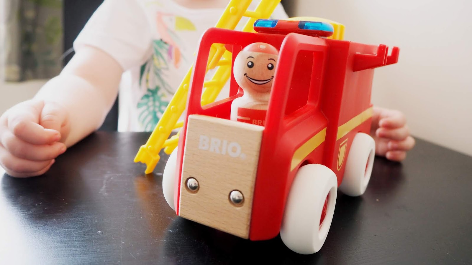 A close up photo of the fire truck toy. The brio logo can be seen on the front, with a wooden man inside the front of the fire truck. Elise is sitting behind.