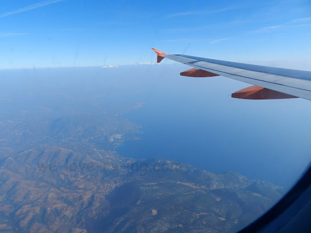 The rugged countryside of Greece can be seen out the airplane window.