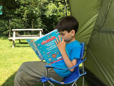 Child reading book outside tent in the shade