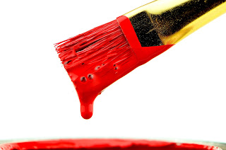 Artist's paintbrush about drip red paint