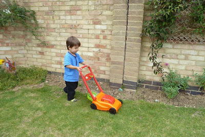 Child cutting the grass with pretend lawnmower
