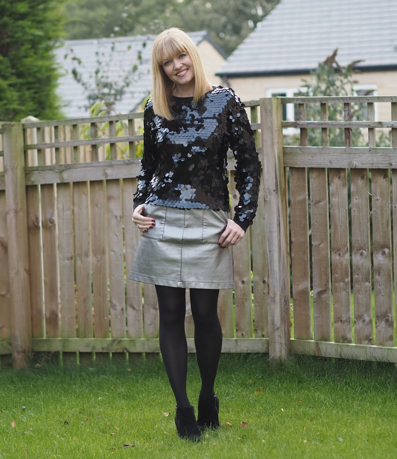 Black paillette sequin sweatshirt, metallic faux leather skirt, ankle boots, over 40