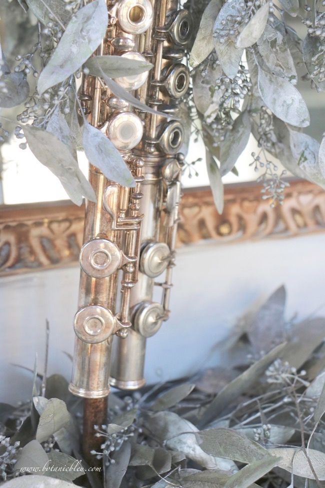 Favorite Christmas carols mantel decorated with flutes and seeded eucalyptus