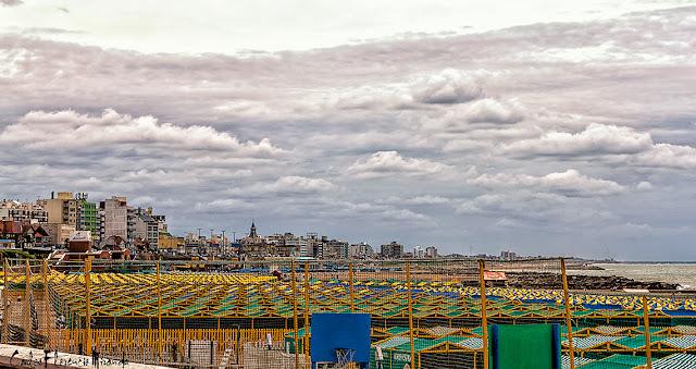Paisaje con carpas de balneario, el cielo encapotado y la ciudad al fondo