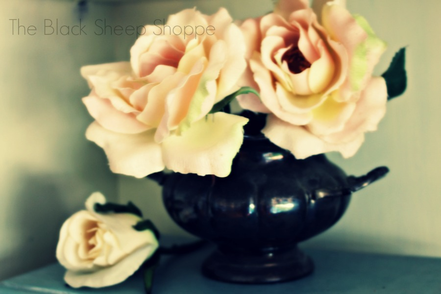 Roses inside an antique silver sugar bowl.