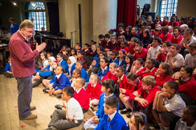 Bach Choir Outreach - David Hill rehearses with the children for 'The World in Folk Song' featuring folk songs from around the world