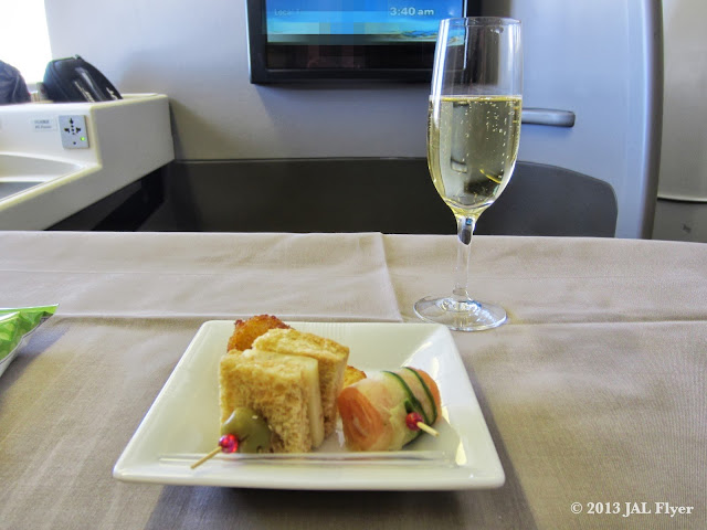 JAL First Class trip report on JL005: Starter served with a glass of Champagne SALON 1999.