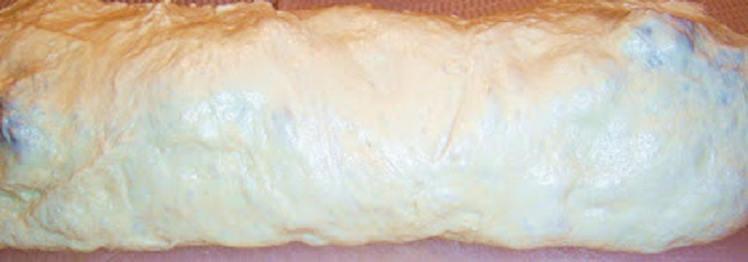 This is a homemade pizza dough stuffed with an Italian green called broccoli rabe with added cooked Italian sausage then added to that filling shredded whole milk mozzarella cheese. It is rolled up and baked into this golden crust then sliced like a sandwich with the filling in the middle.