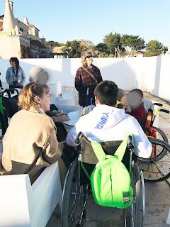 Alunos, professora, educadora conversam no átrio exterior da fortaleza do Farol  Museu