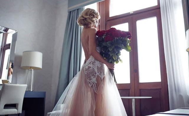 Modelka w przepięknej sukni ślubnej z czerwony bukietem róż.