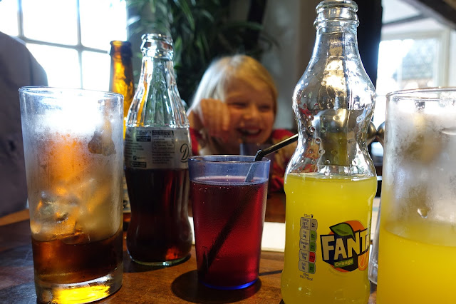 Bottles of soft drink including fanta, diet coke and blackcurrant squash and a young girl grinning in the background