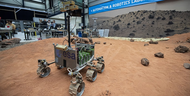 A half-scale version of the ExoMars rover, called ExoMars Testing Rover (ExoTeR), seen manoeuvring itself carefully through the red rocks and sand of 9x9 m Planetary Utilisation Testbed, part of ESA's Planetary Robotics Laboratory in its ESTEC technical centre in the Netherlands, as a test of autonomous navigation software destined for ESA's ExoMars 2020 mission to the Red Planet. Credit: ESA–G. Porter, CC BY-SA 3.0 IGO