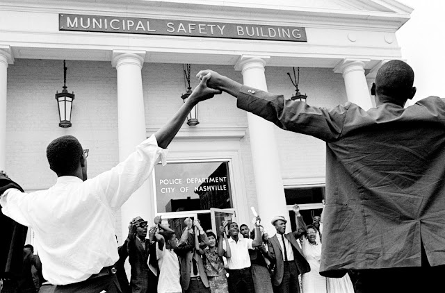 "Demonstrators sing in front of the Nashville Police Department on August 7, 1961, as they protest what they called police brutality in a racial clash two nights earlier. They criticized ""inadequate"" police protection and called for qualified black personnel to ""replace incompetent officers on the police force."""