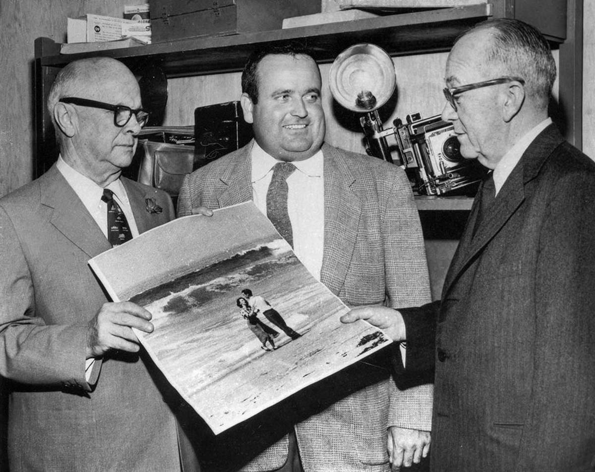 Los Angeles Times photographer Jack Gaunt, center, after winning the Pulitzer Prize, is congratulated by City Editor Bud Lewis, left, and Editor L.D. Hotchkiss.