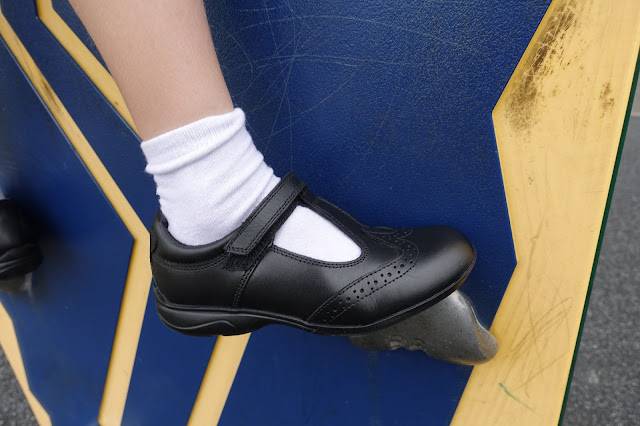 A close up of black t-bar brogue school shoes on a climbing wall