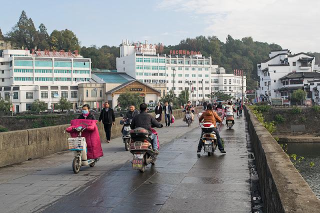 Piétons et scooters sur le vieux pont en pierres de Tunxi