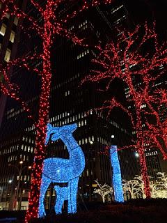 Deer figures of blue lights, bare trees wrapped in red or white lights, near Rockefeller Center, New York, New York