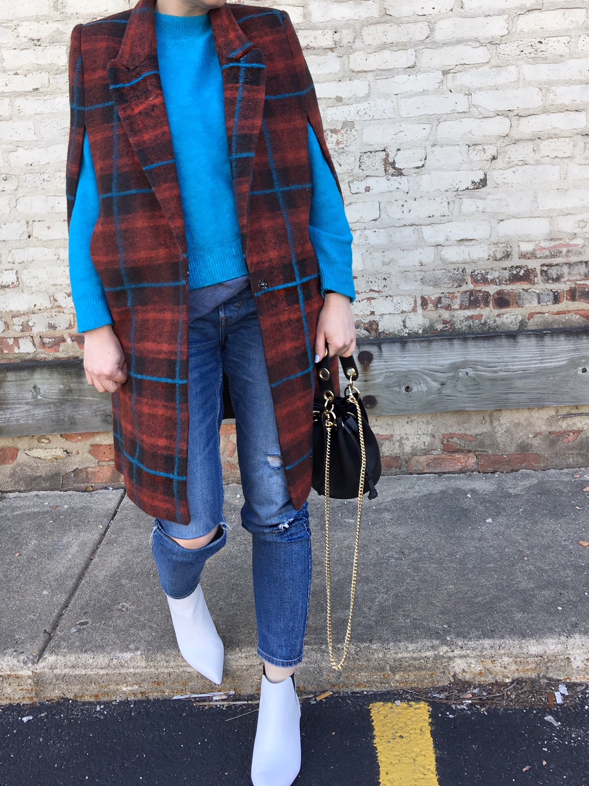 A blue sweater and a plaid cape coat