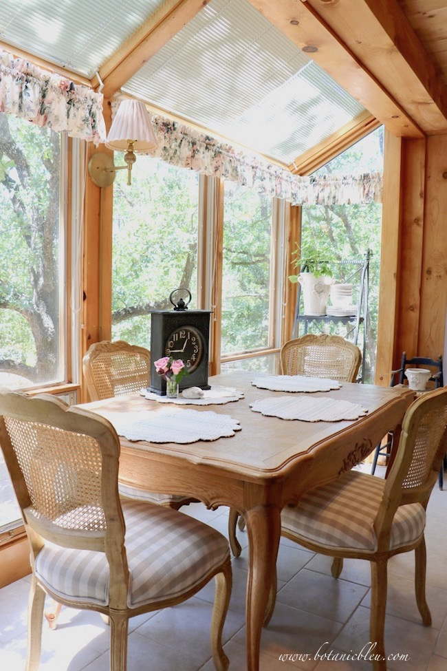 French Country dining chairs with antique French table in breakfast sunspace