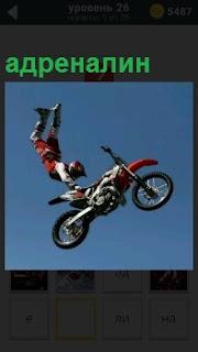 Спортсмен на мотоцикле совершает трюк, высокий прыжок, адреналин в результате зашкаливает у него