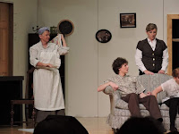 Woman dressed as housekeeper on stage in a play
