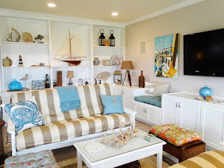 enamor living room with nautical theme decorating on white shelving behind gray white striped sofa and blue fabric decor