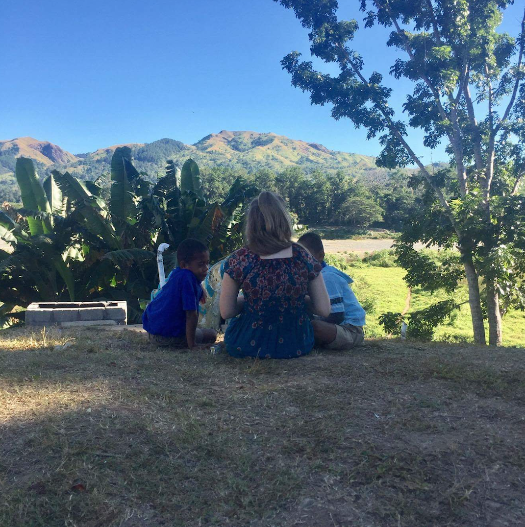 A female volunteer teaching two male students on the grass outside