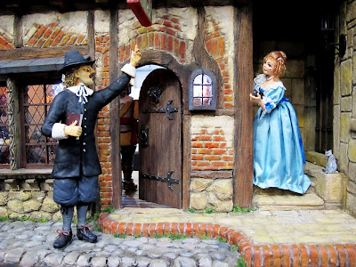 Two figures outside a one-twelfth scale miniature mid 17th-century inn.