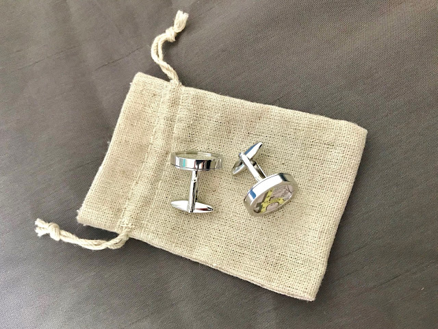 Silver personalised map cufflinks on a small fabric bag