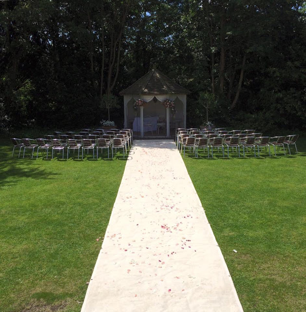 Outdoor British summer wedding with aisle and rose petals