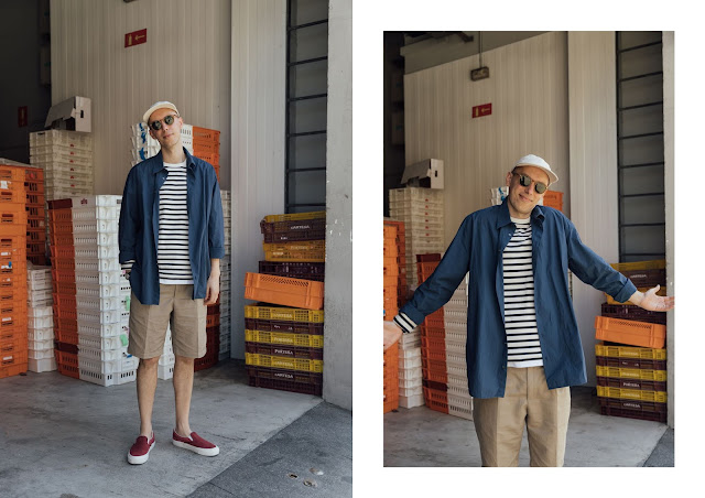 mat buckets wearing spring summer trends by Joseph Fashion, blue stripe breton top with beige pleated shorts, blue poplin shirt and off white baseball cap