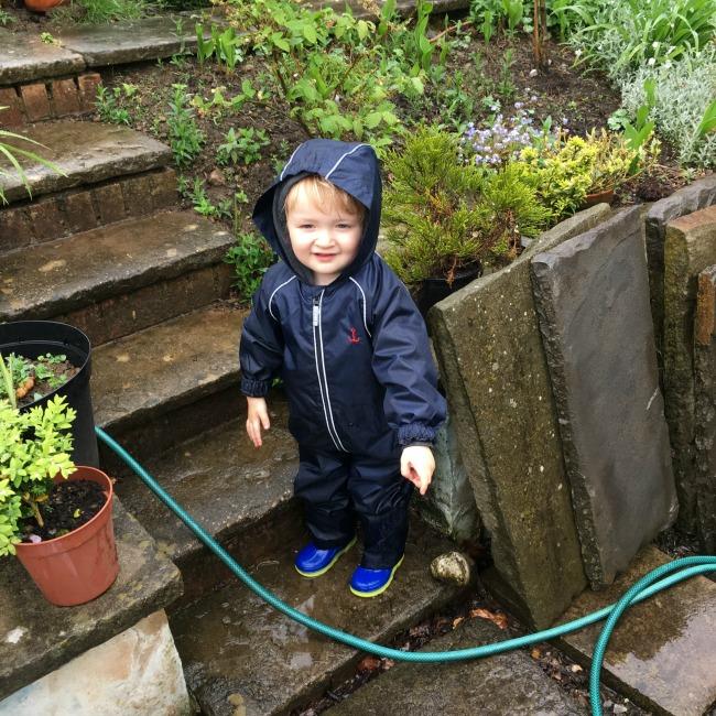toddler in garden in the rain