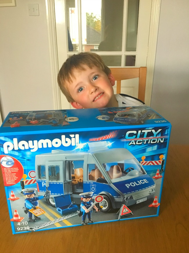 Christmas-gift-guide-2018-boy-grinning-with-Playmobil-policemen-van-box