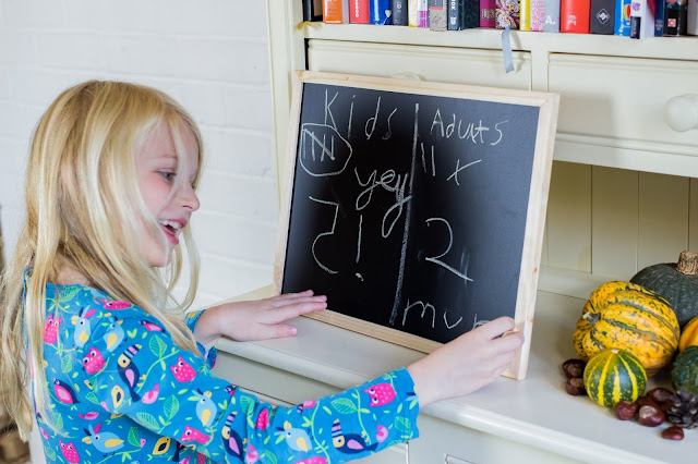 A child writing happily on a blackboard that the children won