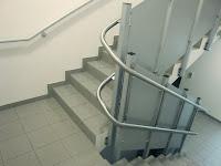 Słupki podtrzymujące tor jezdny platformy schodowej na torze krzywoliniowym