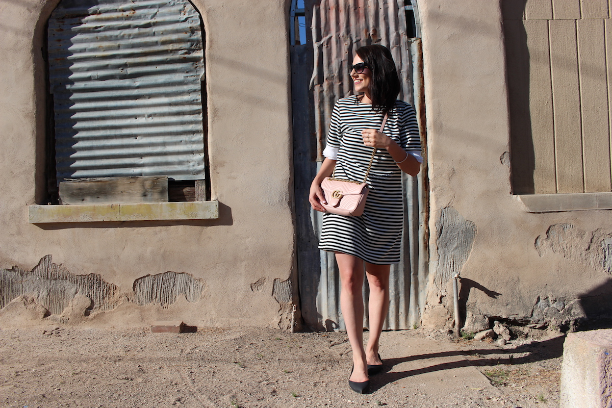 I'm in Barrio Viejo Tucson, wearing a black and white striped dress with my Gucci bag.