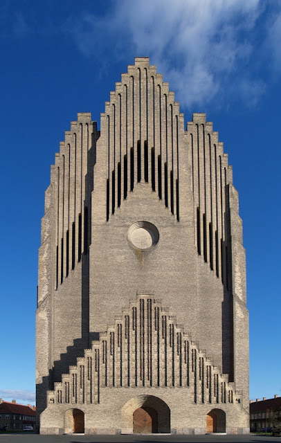 Grundtvig's Church is located in the Bispebjerg district of Copenhagen, Denmark. It is a rare example of expressionist church architecture. Due to its unusual appearance, it is one of the best known churches in the city.  Jensen-Klint's design for Grundtvig's Church is a synthesis of architectural styles. In preparation for the project, the architect studied many Danish village churches, particularly those on the island of Zealand with stepped gables. Their traditional building techniques, materials and decoration inspired his design. Klint merged the modern geometric forms of Brick Expressionism with the classical vertical of Gothic architecture.  The most striking feature of the building is its west facade, reminiscent of a westwork or of the exterior of a church organ. It includes the 49 m (160 ft) tall bell tower. The imposing facade with its strong verticality guides one's eyes towards the sky. The bottom half of the tower is simple brick while the upper reaches present the appearance of one solid, rippling surface. Klint decorated the nave with a version of the stepped gables common on Danish churches, but reinterpreted by doubling the apex. The nave was designed with generous dimensions: The triple-aisled hall church is 76 m (259 ft) long in total and 35 m (115 ft) wide; the nave has a height of 22 m (72 ft).