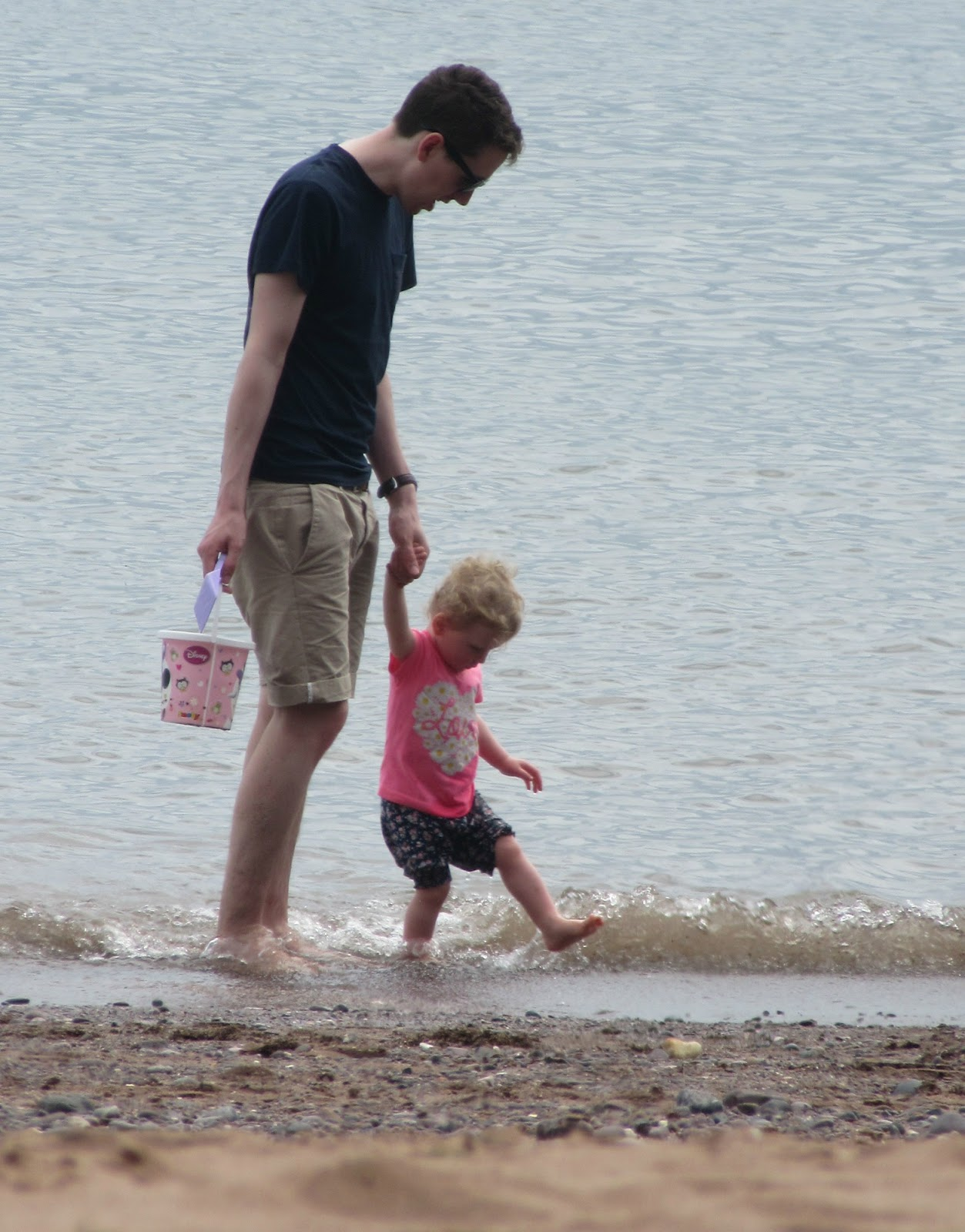 Daddy and daughter walking in the sea