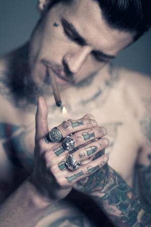 Vemos a un chico tatuado encendiendo un cigarro
