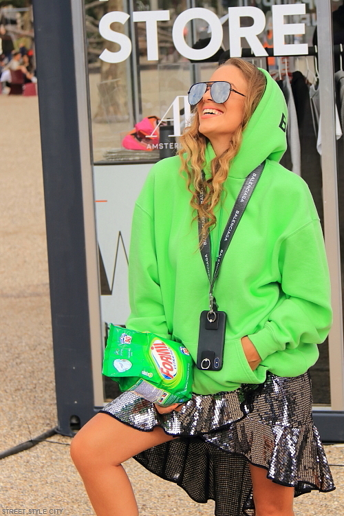 Dutch girl wearing her green neon hoodie and sequin silver metallic skirt in the street at the amsterdam fashion week. Street style fashion.
