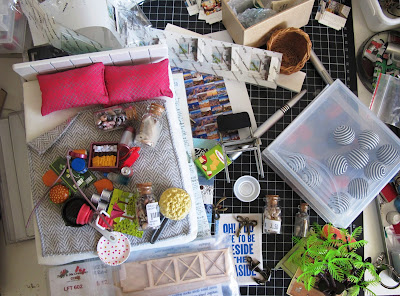 Aerial view of a work table covered with various one-twelfth scale modern miniatures.