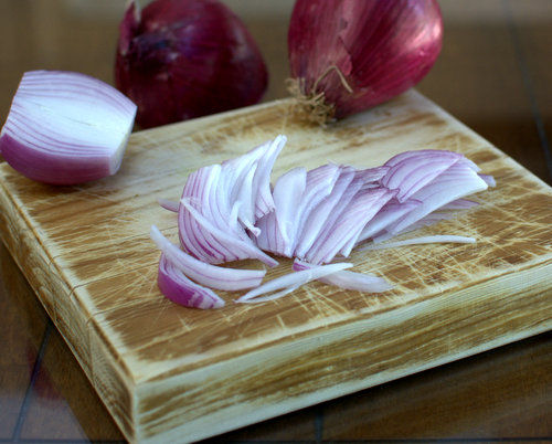 Sliced onions for Spiced Pickled Red Onions ♥ KitchenParade.com, a game changer for tacos, salads, eggs and more.